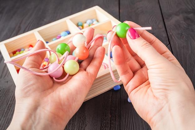 手作りボタンブレスレット。明るい色のボタン、ペンチのセット。 diyバングルジュエリーのアイデア。創造的な工芸品を簡単に作る