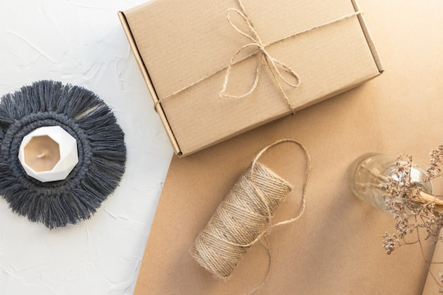 Handmade candle on macrame coaster, present or parcel craft box and jute rope bobbin. organic packing, eco-friendly parcel. dry wild herb in vase. white craft paper background, flay lay, top view.