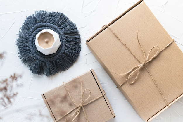 Handmade candle on macrame coaster, two craft boxes with jute bows. organic packing, eco-friendly parcel. dry wild herb. white background, flay lay, top view.