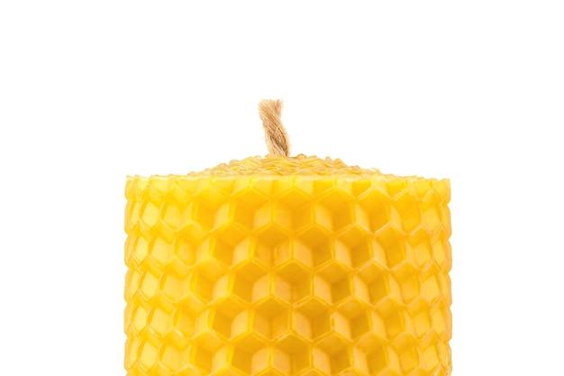 Свеча ручной работы из натурального пчелиного воска на белом фоне