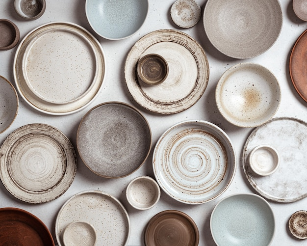 Handmade ceramics, empty craft ceramic plates and bowls on light background, top view