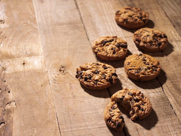 Handmade chocolate chip cookies on a rustic dark wood background