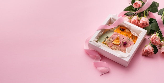 핑크와 장미 꽃다발에 다른 색상의 수제 초콜릿 조각.
