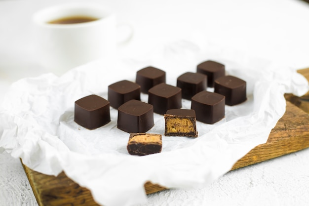 Handmade chocolates candies on white paper, a cup of coffee on the background.