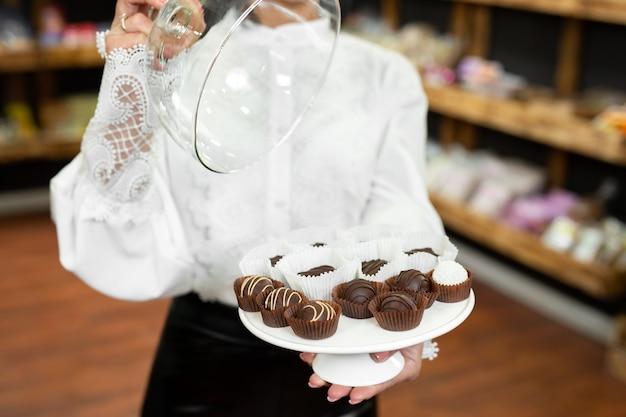 店内の美しい若い女性の手にガラスの蓋の下のトレイに手作りチョコレート