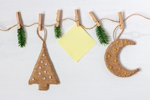 Handmade christmas garland with paper note and jute moon and tree on white background