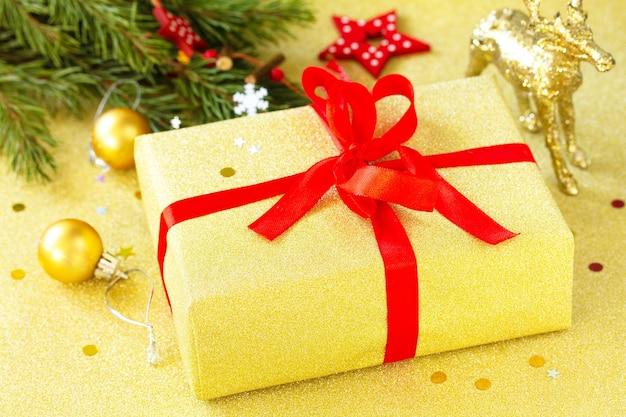 手作りのクリスマスギフトボックスクリスマスプレゼント赤いリボンと木の枝の装飾が施された金色のボックス