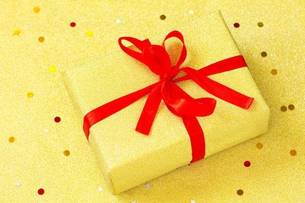 金の背景に手作りのクリスマスギフトボックスクリスマスは赤いリボンと金色のボックスを提示します