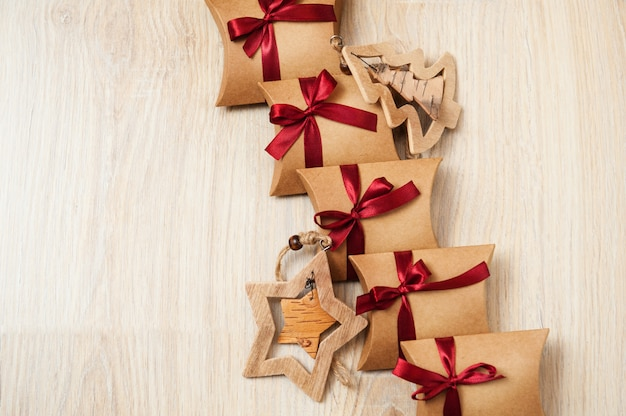 Handmade christmas gifts from kraft paper and wooden toys on the christmas tree