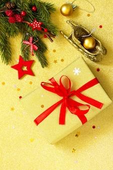 手作りのクリスマスプレゼント赤いリボンと木の枝の装飾が施された金色の箱上面図コピースペース