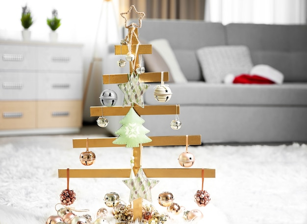 A handmade christmas tree and baubles on the floor in the room
