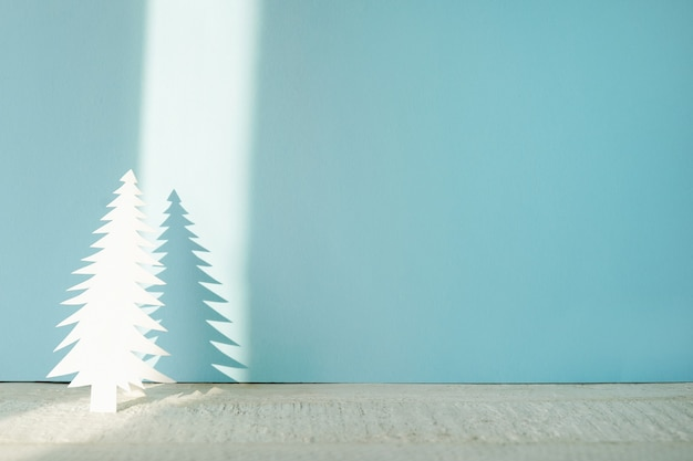 Handmade christmas tree cut out from paper on blue with shadow