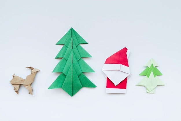 Handmade christmas tree; reindeer; santa claus paper origami isolated on white backdrop