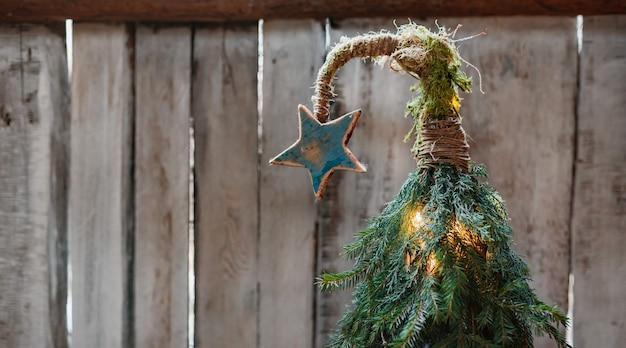 나무 배경에 곡선 된 상단에 스타와 함께 수 제 크리스마스 트리. 저렴한 새해. 최소한의 현대적인 에코 스타일.