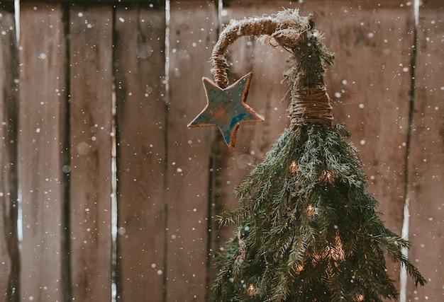 나무 벽에 곡선 된 상단에 스타와 함께 수 제 크리스마스 트리. 저렴한 새해. 최소한의 현대적인 에코 스타일.