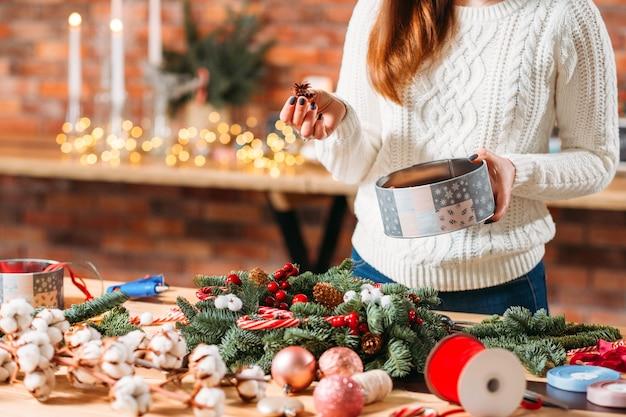 수제 크리스마스 화환. 겨울 장식을 위해 소나무 콘을 사용하는 여성 플로리스트.