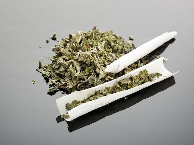 Handmade cigarette with dried marijuana on gray background