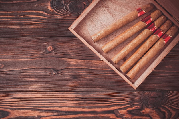 Handmade cigars on a wooden background with copyspace