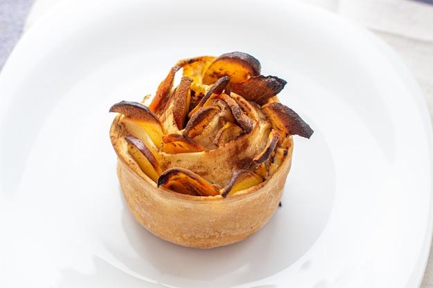 白い皿に手作りのシナモンとリンゴのパン。甘い自家製ケーキ。