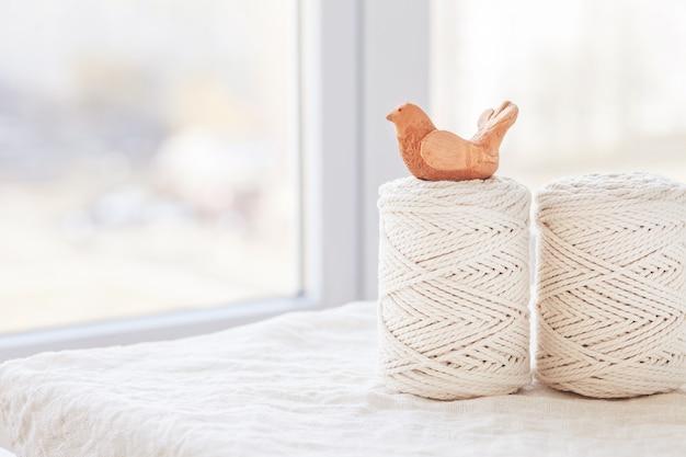 手作りの粘土の鳥とマクラメの編み込みと綿の糸。マクラメや手工芸品のバナーや広告に適した画像。コピースペース