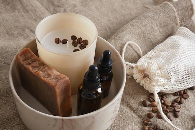 흰색 시트에 수제 코코아 비누, 아로마 버터 또는 세럼, 아로마 양초, 친환경 스파 개념 및 아로마 테라피