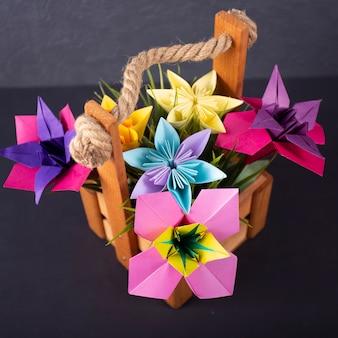 色付きの背景のマクロのスタジオでのバスケットで手作り色の花折り紙花束ペーパークラフトアート
