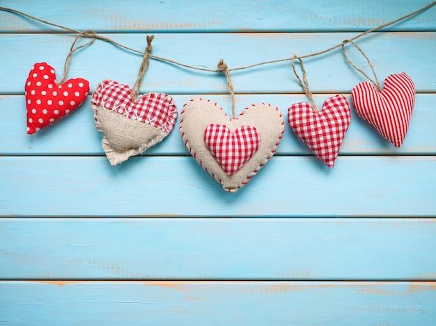 Цветные сердечки ручной работы на синем деревянном фоне