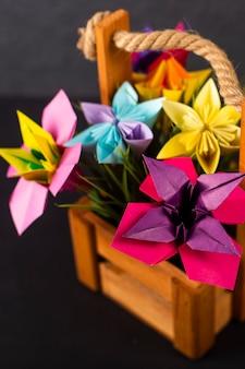 色付きの背景のクローズアップマクロのスタジオで草が付いているバスケットの手作り色紙花折り紙花束ペーパークラフトアート