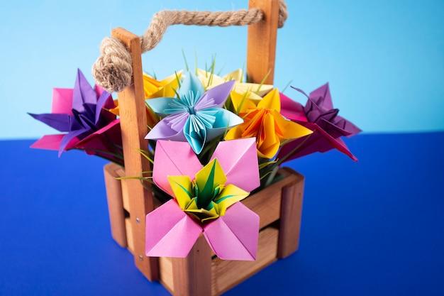 色付きの背景のクローズアップのスタジオで草が付いているバスケットの手作り色紙花折り紙花束ペーパークラフトアート