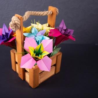 色付きの背景のマクロのスタジオで草が付いているバスケットの手作り色紙花折り紙花束ペーパークラフトアート