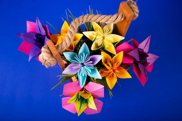 色付きの背景のトップショットのスタジオで草が付いているバスケットの手作り色紙花折り紙花束ペーパークラフトアート