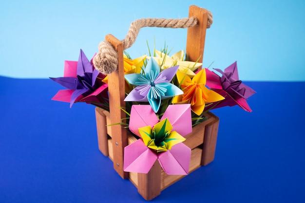 色付きの背景のスタジオで草が付いているバスケットの手作り色紙花折り紙花束ペーパークラフトアート