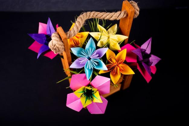 Darkbackgroundのスタジオで草が付いているバスケットの手作り色紙花折り紙花束ペーパークラフトアート