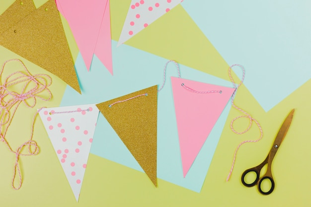 Handmade colorful bunting made with paper and scissor on green background