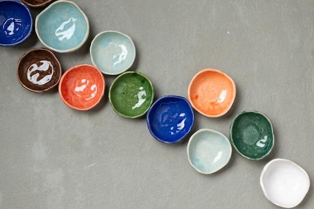 수제 다채로운 세라믹 빈 접시와 접시는 콘크리트 배경, 위쪽 전망입니다. 다양한 작은 그릇 컬렉션