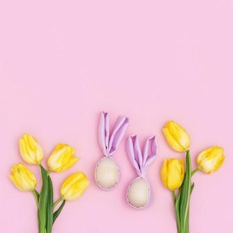 Разноцветные пасхальные яйца ручной работы с ушками кролика и букетом свежих желтых цветов тюльпана