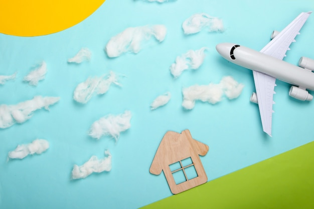 Handmade composition of a house on the lawn and airplane in a sunny sky with clouds