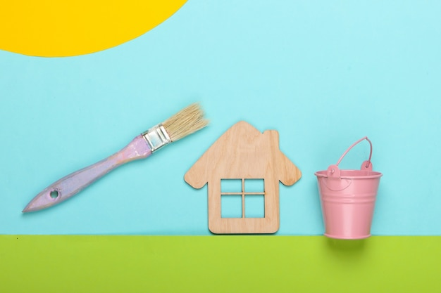 Handmade composition of a house on the lawn and paint brush with bucket at sunny sky day