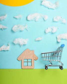 ショッピングカートと芝生の上の家と雲のある晴れた空の手作りの構図。