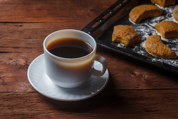 Handmade cookies on a baking sheet and a cup with hot tea or coffee on a wooden surface. the concept of homemade culinary skills.