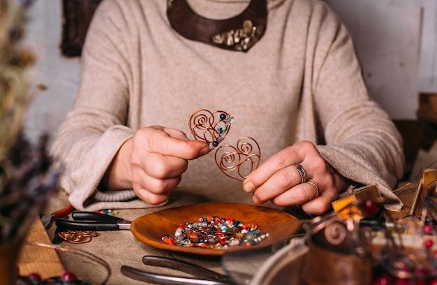 アクセサリーとテーブルの上の手作りの銅線加工工具。手芸人アートコンセプト
