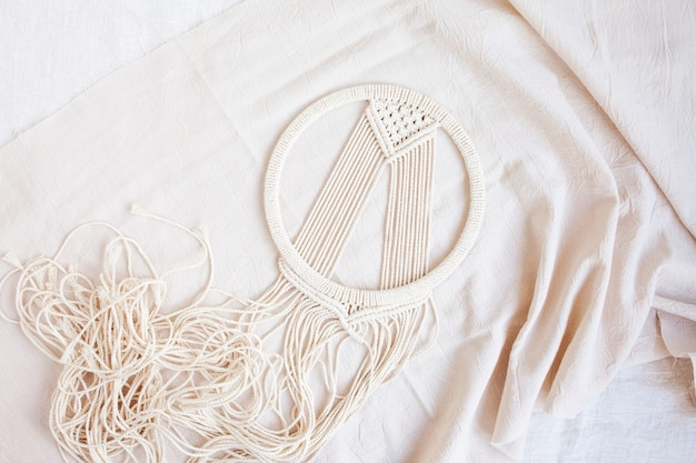 Handmade cotton macrame dream catcher during fabrication. traditional amulet for protecting sleep. Premium Photo