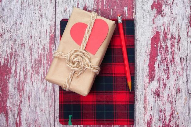 木製の背景にメモ帳で手作りの手作り紙ギフトボックス