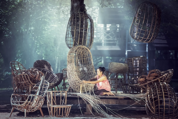 Handmade crafts of a craftsman working rattan chair in countryside of thailand