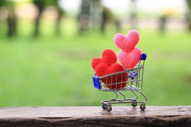 Handmade crochet heart in mini shopping cart on green background for valentines day