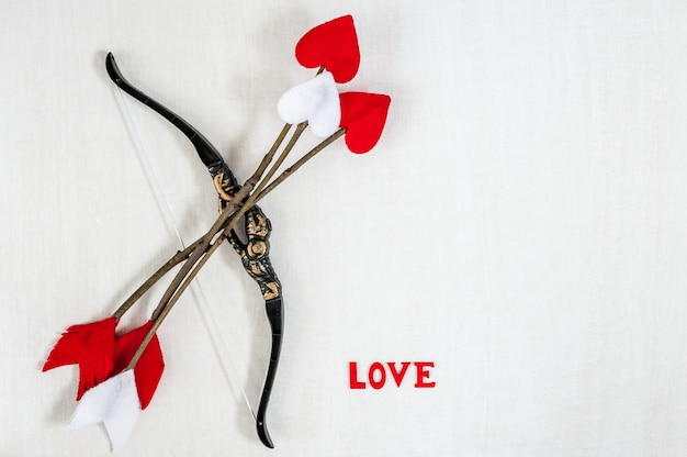 Handmade cupid's twig arrows, bow and letters love on a white wooden background.
