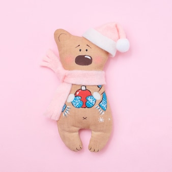 Handmade cute teddy bear santa on pink