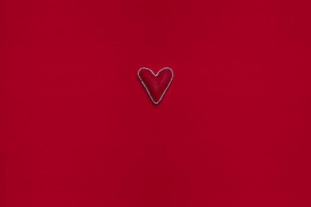 フェルトの表面に手作りのdiyハート。プレスウール、ファブリック、スレッド。 2月14日バレンタインデー