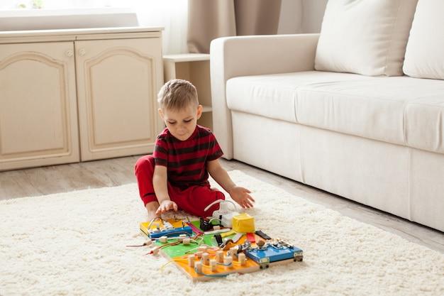 手作りのdiy感覚の子供のおもちゃ、3歳の男の子が忙しいボードで遊ぶ
