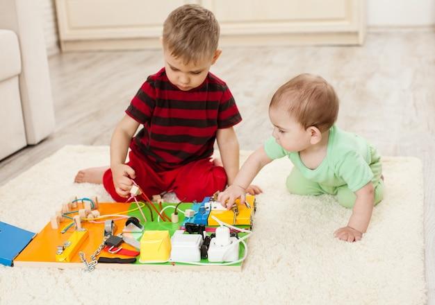 手作りのdiy感覚の子供のおもちゃ、2人の兄弟が忙しいボードで遊ぶ